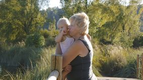 Middle aged grandmother holds her blonde baby girl standing on wooden bridge in natural park stock footage