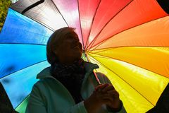 Middle aged grey haired woman holding colorful umbrella outside on a sunny day royalty free stock photography