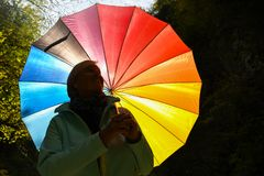 Middle aged grey haired woman holding colorful umbrella outside on a sunny day stock photos