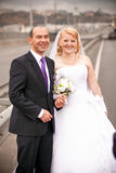 Middle aged groom and bride walking on highway Stock Image