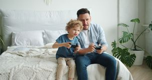 Middle-aged guy playing video game with happy child sitting on bed at home stock video