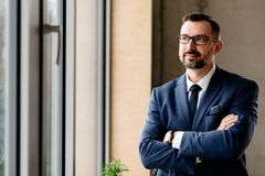 Middle aged handsome businessman in suit at office stock images