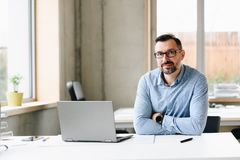 Middle aged handsome man in shirt working on laptop computer in office. Man working in office stock photos