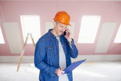 Manual worker using handy on the construction site Royalty Free Stock Photography