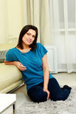 Middle-aged happy smiling woman sitting on the floor Royalty Free Stock Images