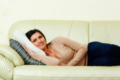 Middle-aged happy woman lying on the sofa Royalty Free Stock Photo