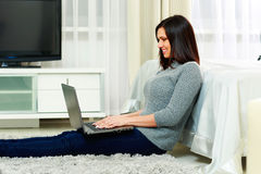 Middle-aged happy woman sitting on the floor and using laptop Royalty Free Stock Photos