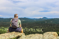 Middle aged hiker man sitting on rock looking at horizon. Man sitting atop a mountain looking at horizon, wearing hiking clothing and backpacking gear Royalty Free Stock Images