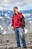 Middle-aged hiker tells about seen landscape in the mountain, talking on mobile phone Stock Photography