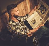Middle-aged hipster reading newspaper in barber shop Royalty Free Stock Images
