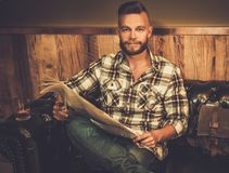 Middle-aged hipster reading newspaper in barber shop Stock Image