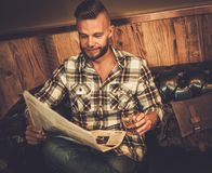 Middle-aged hipster reading newspaper in barber shop Stock Images