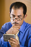 Middle-aged Hispanic businessman texting. Close-up of middle-aged Hispanic businessman staring at text message on mobile phone Stock Image