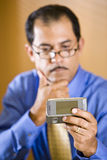 Middle-aged Hispanic businessman texting. Close-up of middle-aged Hispanic businessman staring at text message, handing holding mobile phone in focus Stock Photography