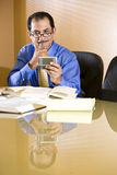 Middle-aged Hispanic businessman texting. Close-up of middle-aged Hispanic businessman reading text message on mobile phone Stock Images