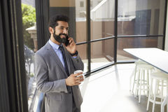 Middle aged Hispanic businessman using phone and holding cup royalty free stock photo