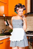 Middle-aged housewife in kitchen with bottle and glass of wine. Beautiful woman in the kitchen with bottle and glass of wine Stock Photography