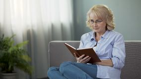 Middle-aged housewife sitting on sofa and reading interesting book, hobby. Stock footage stock video footage