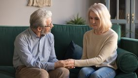Middle aged husband holding hands, caressing upset wife at home stock photo