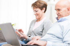 Middle-aged husband and wife surfing the internet Stock Image