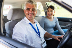 Middle aged instructor student. Middle aged driving instructor sitting in a car with student driver royalty free stock photography