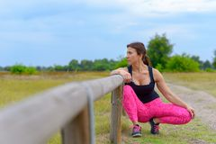 Middle aged jogger leaning on guard rail. Middle aged female jogger leaning on and crouching by guard rail at the side of dirt road in open field stock photos