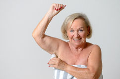 Middle Aged Lady Applying Deodorant on Armpit Stock Photo