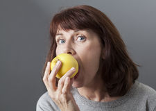 Middle aged lady crunching into some fruit. Health fitness - beautiful mature woman biting yellow golden apple for vitamins diet and skin health stock image