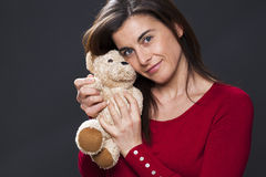 Middle aged lady peacfully enjoying her cuddly toy Stock Image