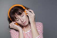 Middle aged lady peacfully enjoying music. Listening concept - serene mature woman with headphone on for relaxation stock photo