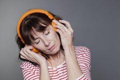 Middle aged lady peacfully enjoying music Stock Photo