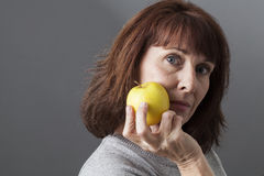 Middle aged lady presenting us some fruit. Health concept - thinking beautiful mature woman holding a yellow golden apple for vitamins diet royalty free stock photos
