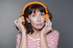 Middle aged lady pulling headphone away from ear Stock Image
