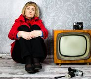 Middle aged lady sitting on old floor. Next to retro tv and photo camera Royalty Free Stock Image