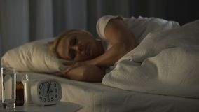 Middle-aged lady suffering from bad sleep and health, problem of aging, insomnia. Stock footage stock video footage
