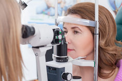 Middle aged lady is visiting oculist in clinic. Cheerful woman is having eye exam performed by the ophthalmologist. She is looking into the slit lamp with joy stock photo