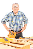 Middle aged male carpenter standing behind working table Stock Images