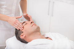 Middle-aged male client getting treatment at beauty salon. Senior man is enjoying facial massage at spa. He is lying with relaxation Royalty Free Stock Images