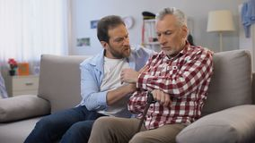 Middle-aged male comforting retiree father, suffering loss of wife, depression