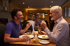 Middle aged male couple eating evening meal in a restaurant Stock Photography