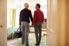 Middle aged male couple walk in to a hotel room, back view Stock Image