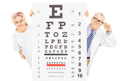 Middle aged male doctor and female patient standing behind eyesi Royalty Free Stock Photos