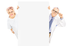 Middle aged male doctor and female patient standing behind panel Royalty Free Stock Image