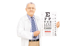 Middle aged male optician holding eyesight test and pointing wit Royalty Free Stock Photography