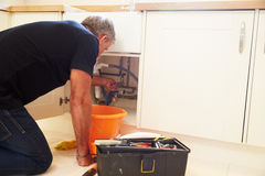 Middle aged male plumber fixing a kitchen sink royalty free stock photo