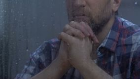 Middle-aged male praying god behind rainy window, hoping for better, belief stock footage