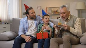 Middle-aged male and preteen boy congratulating grandpa with anniversary, family