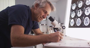 Middle aged male radiologist looking through microscope. Stock Image