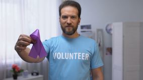 Middle-aged male volunteer holding purple ribbon, Alzheimer disease awareness stock video