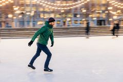Middle aged male wears figure skates, being at ice rink in winter park, has fun with friend. Athlete speed skater demonstrates hi royalty free stock image